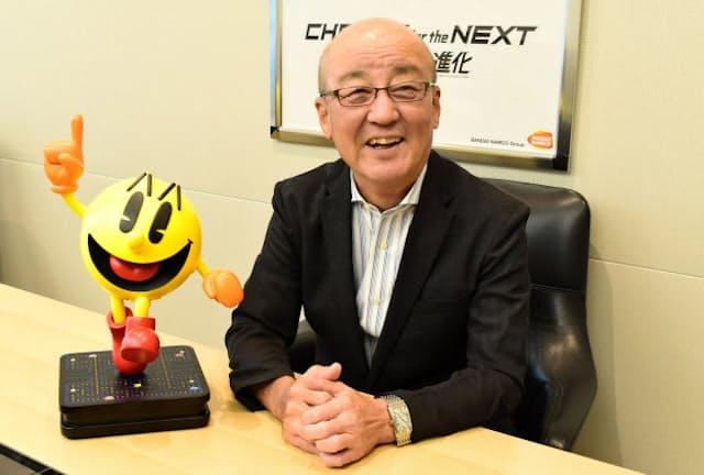 ナムコが生んだ大ヒットゲーム「パックマン」のキャラクターを前に微笑む石川氏