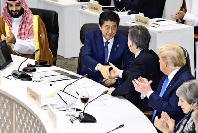 G20大阪サミットで「大阪首脳宣言」を採択し、出席者と握手する安倍首相=手前左から2人目(6月29日、大阪市)=共同