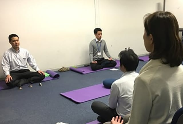 佐渡医師(左)の指導で、瞑想して今の心の状態を見つめる(現在はオンライン開催)=東京都新宿区の慶応大学ストレス研究センター