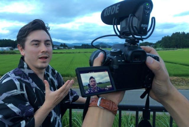 カメラの前で弁が立つブロード氏。背景の選定にも余念がない