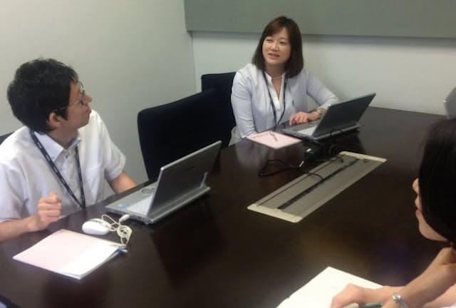 夫の転勤地で働く片岡寛子さん(中)は毎月1回、東京に来て顧客や同僚と打ち合わせする(東京・品川のニコンシステム)