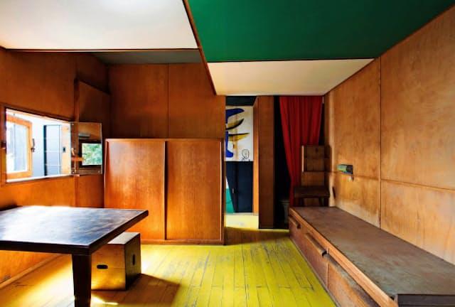 縦横366センチ四方の部屋。左奥の服入れの裏側に、入り口に通じる廊下がある。右奥には極小のトイレ。その手前が木製ベッド。台所や浴室はなく、食事は隣の食堂で、風呂は外にある簡易シャワーで済ませていた