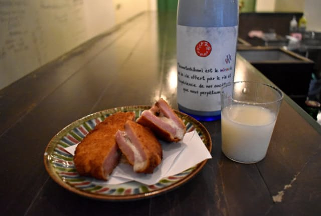 東京・恵比寿の日本酒バー「GEM by moto(ジェムバイモト)」が提案するブルーチーズを挟んだハムカツとどぶろくの組み合わせ。熱々にとけたチーズとサクサクの衣を柔らかなどぶろくが包み込む