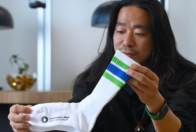 「コンビニエンス ウェア」のロゴが入ったラインソックス。「ブランドのシンボリックな存在としてどうしても作りたかったのがコレ」と話す、ファッションデザイナーの落合宏理さん(東京・港のファミリーマート本社)
