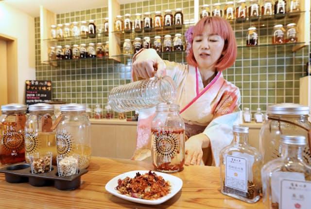 ガラス瓶にクコの実を入れ、ホワイトリカーを注ぐ「薬酒・薬膳酒協会」の保科有理さん(東京都中央区の食医心方)