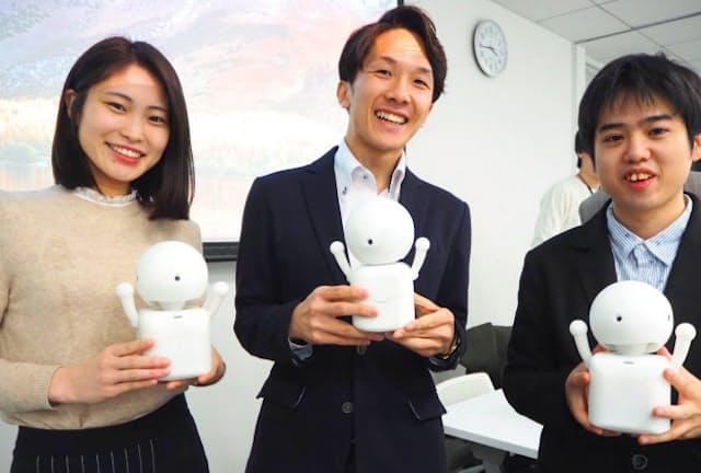 仲間たちと開発中のロボットを抱える大澤さん(中央)「ドラドラ」という言葉だけで人間とコミュニケーションする