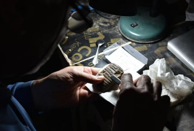 ウル遺跡での調査に参加しているコレージュ・ド・フランスのアッシリア学者、ドミニク・シャルパン氏が、アメリカ・イラク合同チームが発掘したくさび形文字が刻まれた板を調べている。(Photograph by Mahan Kalpa)