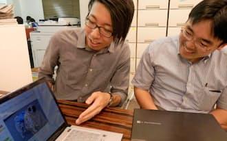 自らの犬グッズ販売サイトを同僚にみせるエンファクトリーの山崎さん(左)(東京都渋谷区)