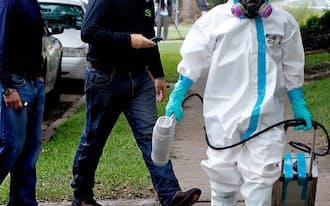 米国内でエボラの診断を受けた看護師の住居周辺で作業を終えた男性ら(12日、米テキサス州)=ゲッティ共同