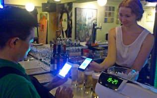スマホで簡単に決済できるようになる(東京・六本木でビットコインを使う客(左))