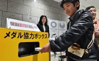 小型電子機器の回収ボックスに不要になった携帯電話を入れる人たち(3月24日、都庁)