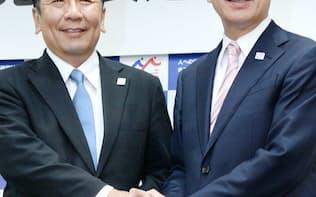 共同記者会見で握手する前原氏(右)と枝野氏(21日、民進党本部)