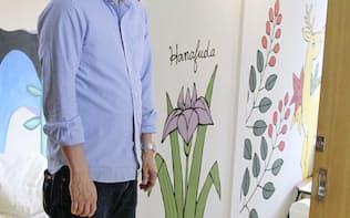芸術家がデザインしたゲストハウス「日進月歩」の室内を説明する支配人の吉崎弘記さん(12日、川崎市川崎区)