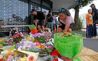 事件があったモスクの近くで犠牲者を悼み献花する人々(16日、クライストチャーチ)=ロイター