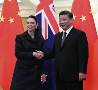 中国の習近平国家主席(右)との会談を前に握手するNZのアーダーン首相(1日、北京)=AP