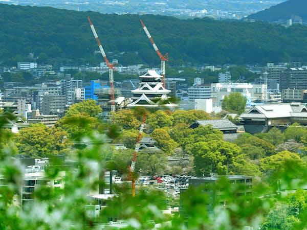 新緑の中に浮かび上がる熊本城。熊本地震で大きな被害を受け、復旧工事が進む=中尾悠希撮影