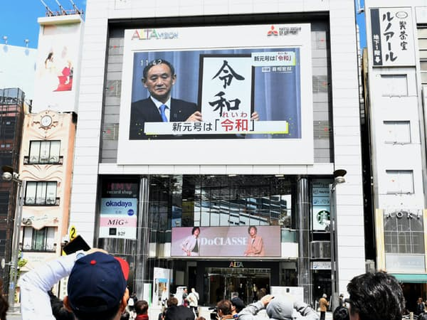 新元号「令和」を伝えるニュース画面を見る人たち(1日、東京都新宿区)