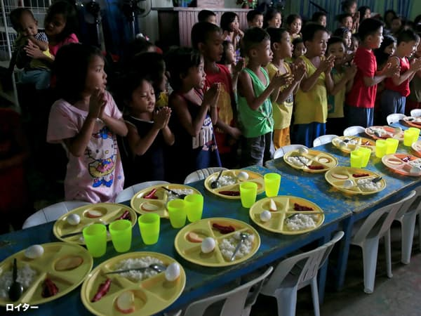 無料の食事を食べる前に祈りを捧げる子供たち(マニラ)=ロイター