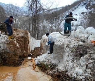1メートル超の積雪のなか、漏水した管を掘り返す作業は難航した(3月、北海道古平町)