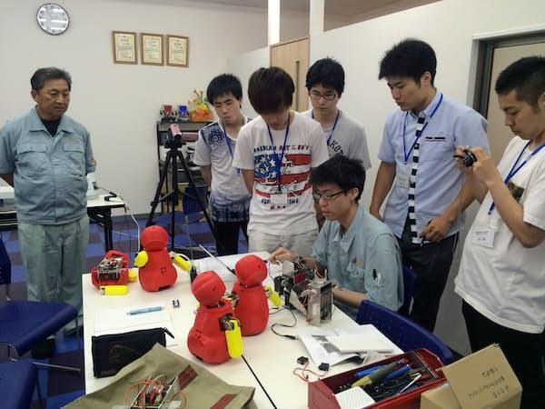「有志の会 八尾」では地元の大学生も交えてロボット開発に取り組んだ(左が藤原さん)