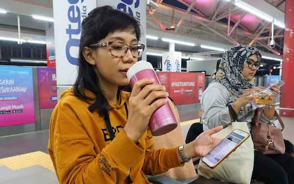 アプリで断食の時間が終わったのを確認し水を飲む女性(9日、ジャカルタ南部)