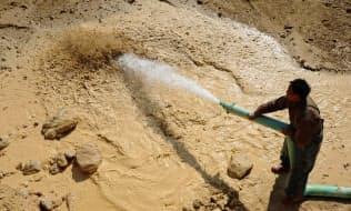 レアアースの鉱山で散水する労働者(中国江西省撫州市)=ロイター