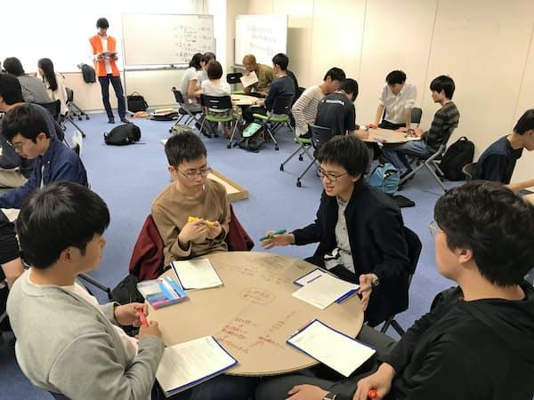 学生は膝の上の円形の段ボール板に紙を載せ、意見を書き込んだ(5月、東工大大岡山キャンパス)