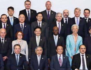 記念撮影する麻生財務相(前列右から2人目)、日銀の黒田総裁(同3人目)ら=9日、福岡市
