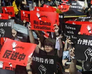 16日、台北での抗議集会で、香港の学生とともに「逃亡犯条例」改正案に抗議する台湾の人々=AP