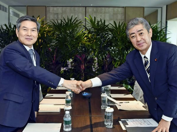 非公式会談で握手する岩屋防衛相(右)と韓国の鄭景斗国防相(1日、シンガポール)=韓国国防省提供・共同