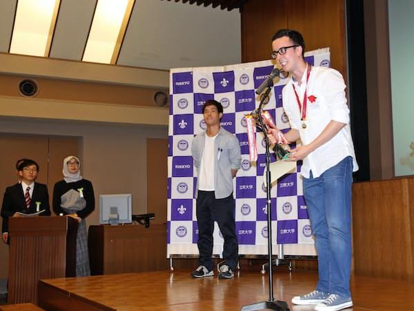 リカルドさん(壇上右)は鎌田さん(同左)の協力を得て日本語スピーチコンテストに参加した(6月22日、立教大池袋キャンパス)