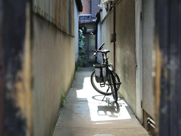昼間でも静けさを保つ京都の人家。路地に止められた自転車に光が差した=小園雅之撮影