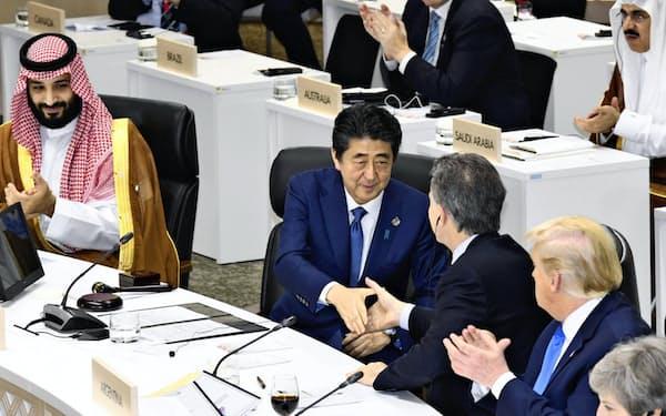 G20大阪サミットで「大阪首脳宣言」を採択し、出席者と握手する安倍首相(手前左から2人目)=29日、大阪市