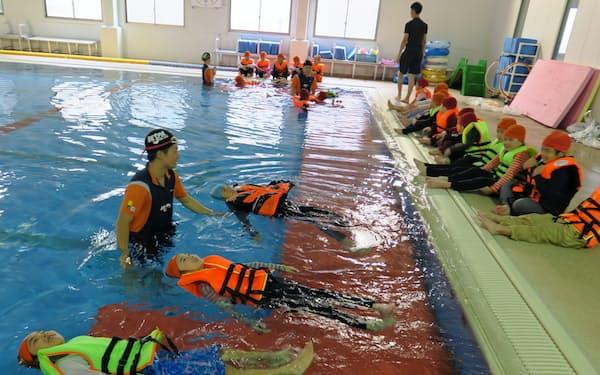 ライフジャケットを着て水に浮かぶ練習をする児童ら(2日、三重県松阪市)