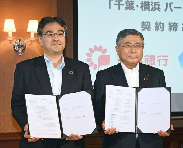 業務提携を発表し、契約書を交わした横浜銀行の大矢頭取(左)と千葉銀行の佐久間頭取(10日、東京都中央区)