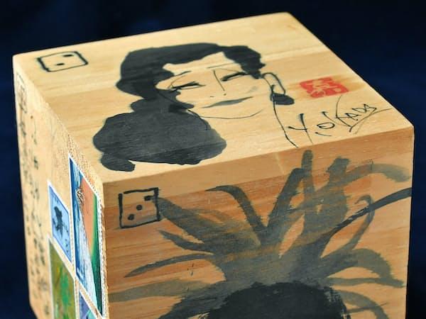 一辺10センチの立方体の四面に女性の顔が描いてある