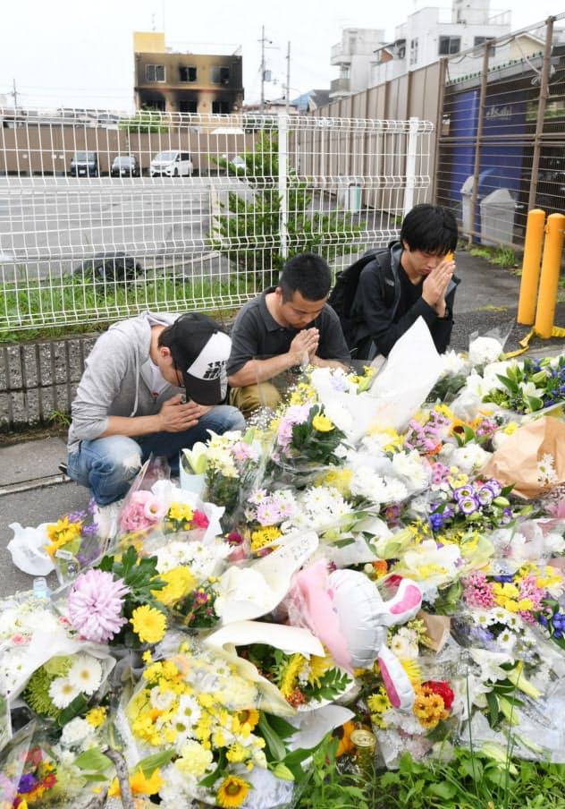 放火火災で多数の犠牲者がでた京都アニメーションのスタジオ(奥)の近くで手を合わせる人たち(20日午前、京都市伏見区)