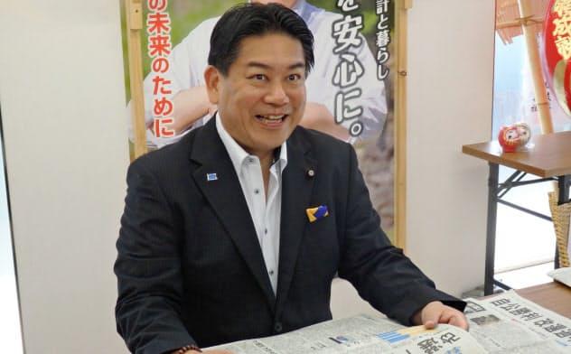投開票から一夜明け、新聞を読む羽田氏(22日朝、長野市)