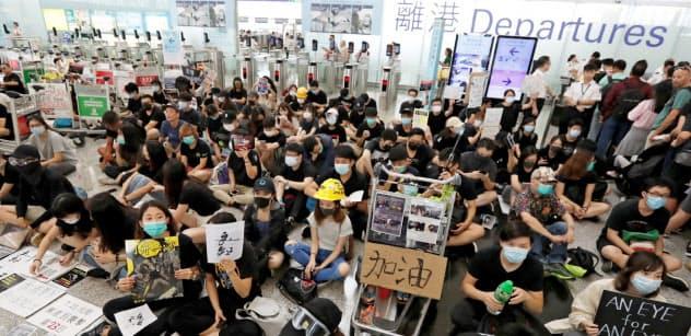 13日、香港国際空港の出発ゲート前に座り込むデモ参加者=ロイター