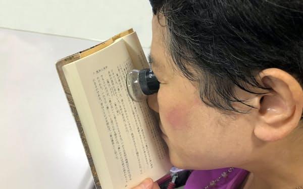ルーペを使って本を読む芳賀さん=日本点字図書館提供