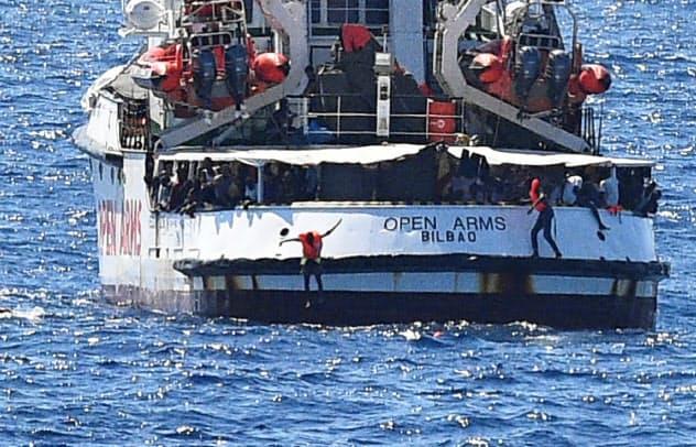 スペインの救助船から海に飛び込む移民(20日、イタリア南端ランペドゥーザ島付近)=ロイター