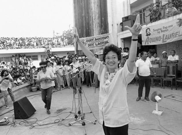 ラバン(闘う)を意味するLのサインを掲げるコラソン・アキノ氏(右)(1986年1月、フィリピン・コロナダル)=AP
