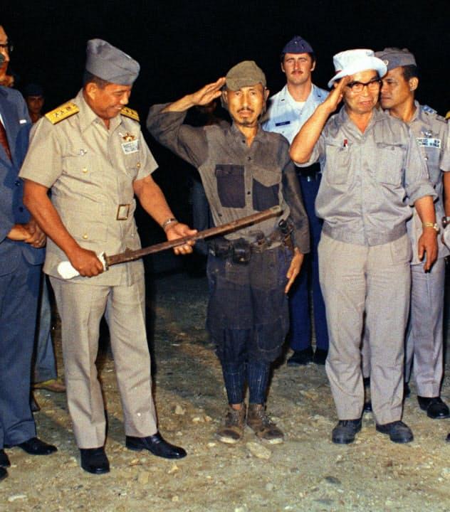 ランクード・フィリピン空軍司令官(左)に軍刀を渡し挙手の礼をする小野田さん(1974年3月、フィリピン・ルバング島)=共同