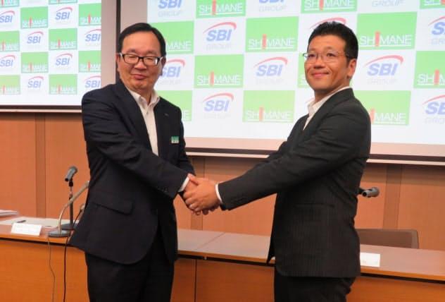 記者会見後に握手する島根銀の鈴木頭取(左)とSBIホールディングスの森田専務(6日、松江市の島根銀本店)