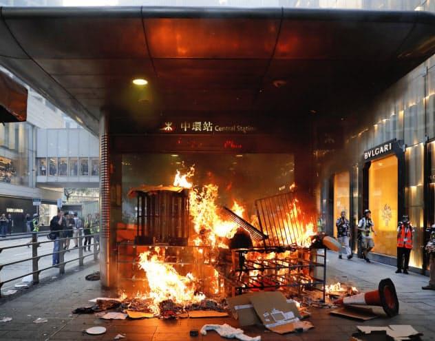 デモ隊はブランド店が集積する中環駅に火を放った(8日、香港)=AP