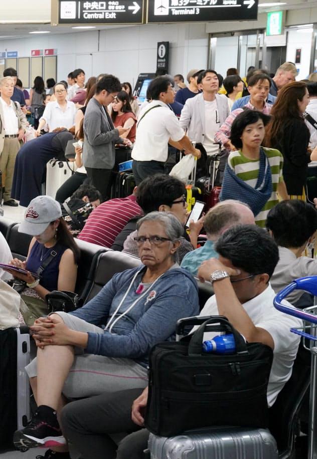 成田空港の到着ロビーでうなだれる外国人利用客(9日)