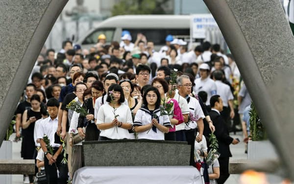 原爆慰霊碑の前で手を合わせる人たち(8月6日、広島市の平和記念公園)