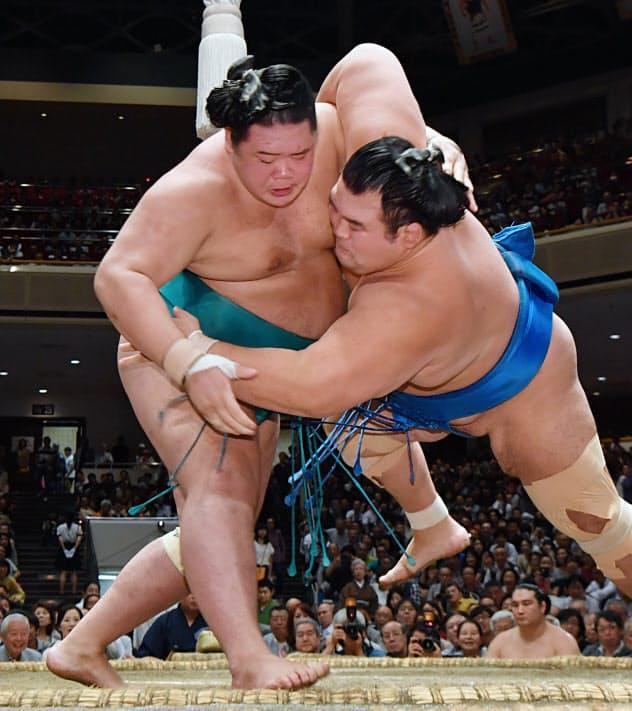 琴奨菊(右)をすくい投げで破る明生