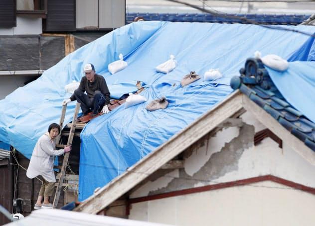 住宅で、シートで屋根を覆う作業をする住民(15日、千葉県館山市布良地区)