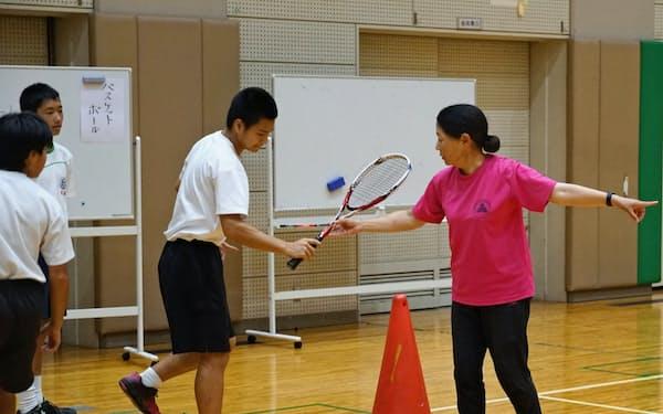 ソフトテニス部の指導をする部活動指導員の新上さん(右)(港区立御成門中学校)